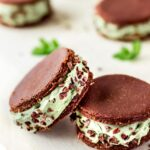 Close up view of vegan ice cream sandwiches against a white background decorated with mint leaves. The sandwiches contain layers of mint ice cream between raw chocolate cookies and are decorated with cacao nibs.