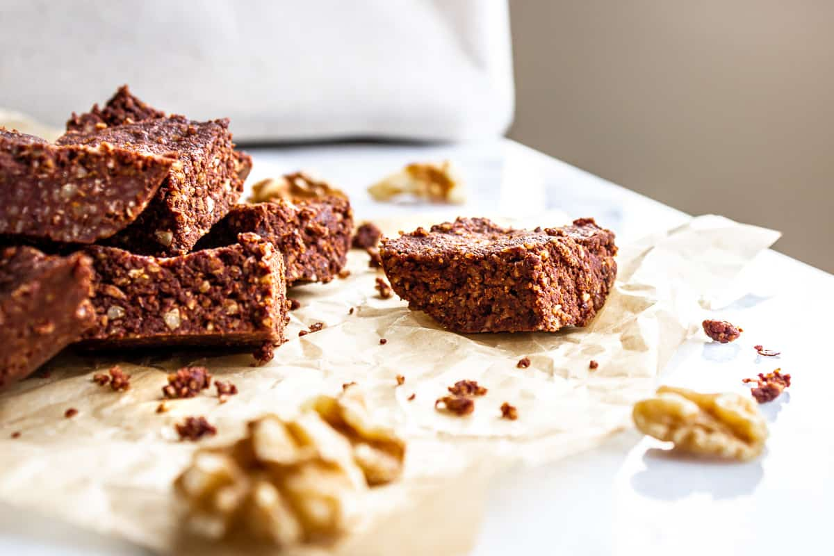 Image of brownies on the side of a white marble table. The brownies are sitting on baking parchment and walnuts are scattered around them.