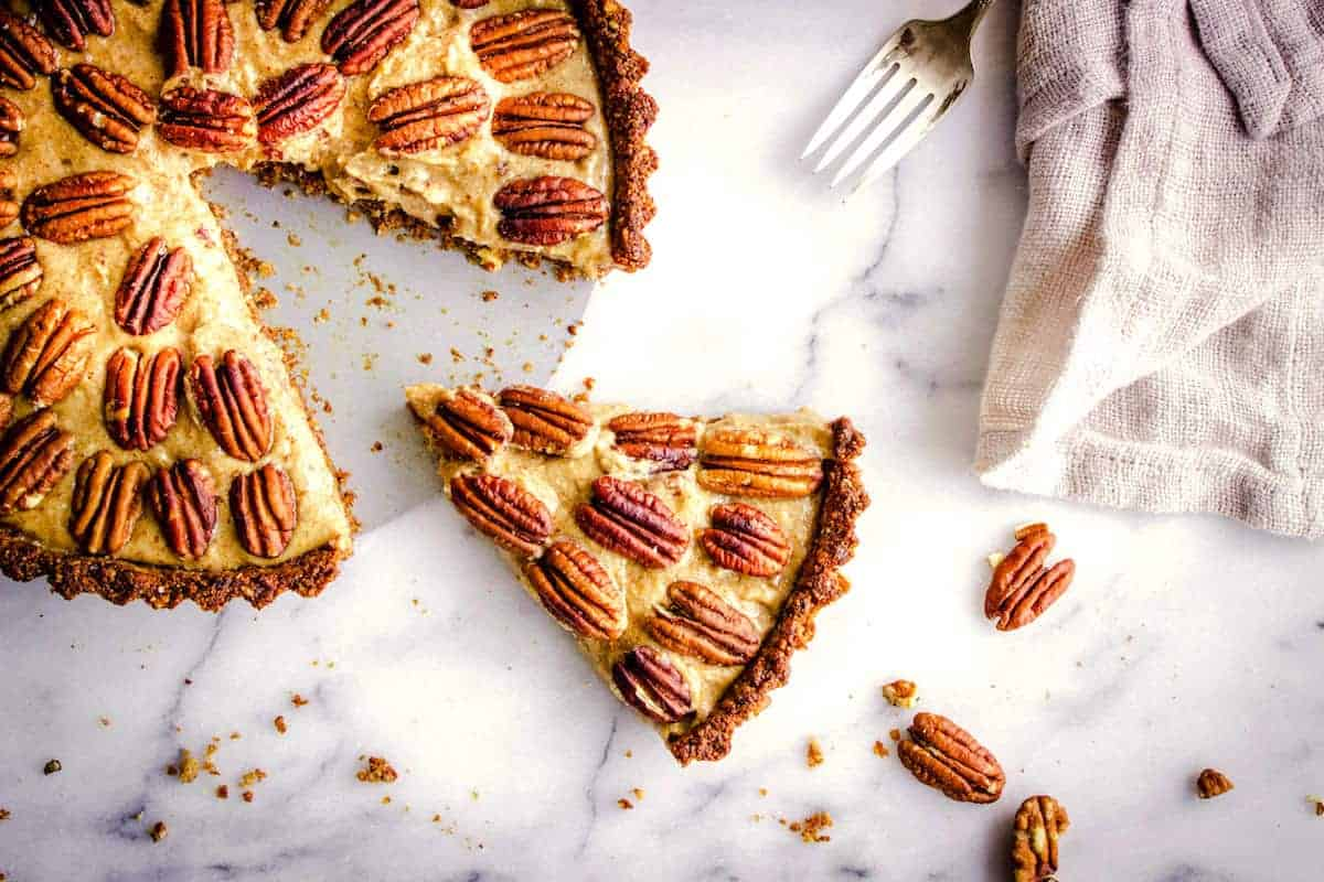 Close up overhead shot of a vegan, gluten free pie decorated with pecans, and sitting on a white marble surface. A slice has been taken out of the pie and beside it sits a linen napkin, a silver fork and some pecan pieces.