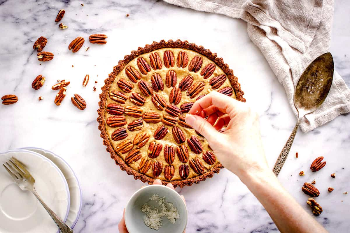 Overhead shot of Easy Vegan Pecan Pie sitting on a white marble background. A woman's hand is sprinkling sea salt flakes over it, and the pie is decorated with concentric circles of pecans. Surrounding it are a beige linen napkin, silver cutlery, small plates and some pecan halves.