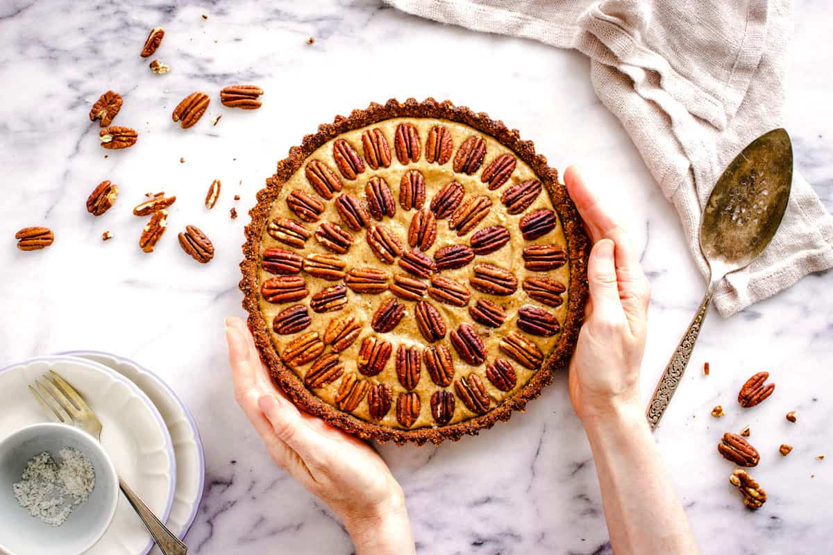 Overhead shot of a vegan, gluten free pie decorated with concentric circles of pecans, sitting on a white marble surface. A woman's hands are holding the pie, and beside it sits a linen napkin, silver cutlery, white plates and some pecan pieces.