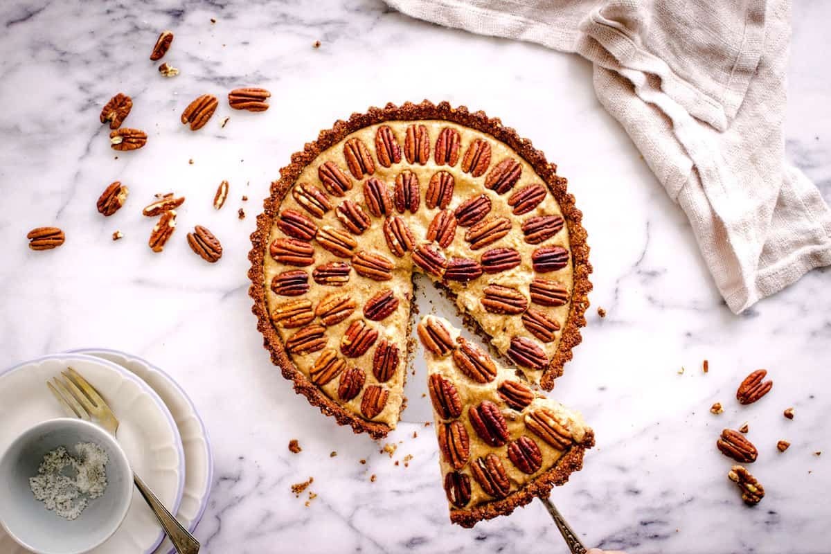 Overhead shot of Easy Vegan Pecan Pie sitting on a white marble background. A slice has been taken out of the pie, and it is decorated with concentric circles of pecans. Surrounding it are a beige linen napkin, silver cutlery, small plates and some pecan halves.