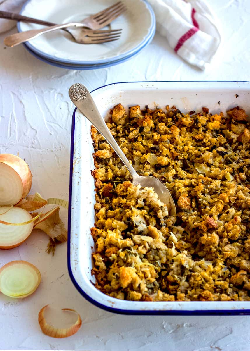 Overhead shot of Easy Vegan Stuffing in a white enamel dish. A woman's hand is spooning some of the stuffing out, and there are slices of bread, a tea towel and a sliced onion nearby.