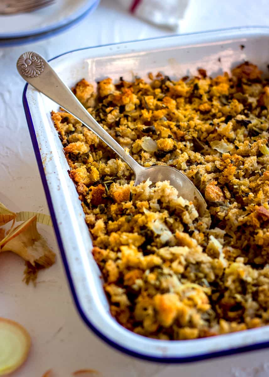 Close up of Easy Vegan Stuffing in a white enamel dish. A silver spoon is nestled in it and there are plates, a tea towel and a sliced onion nearby.