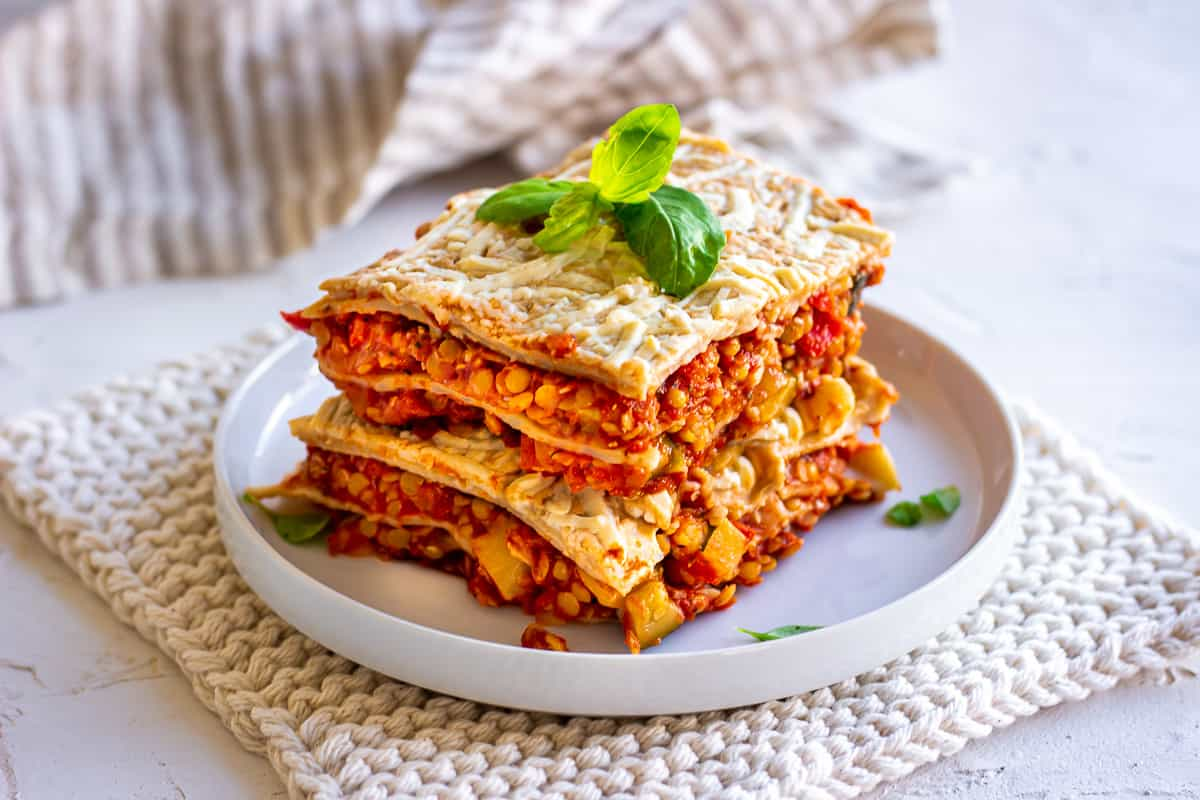 Vegan lasagna - an easy recipes for meal prep, sitting on a white plate and cloth. The lasagna has several layers and is topped with vegan cheese sauce and basil.