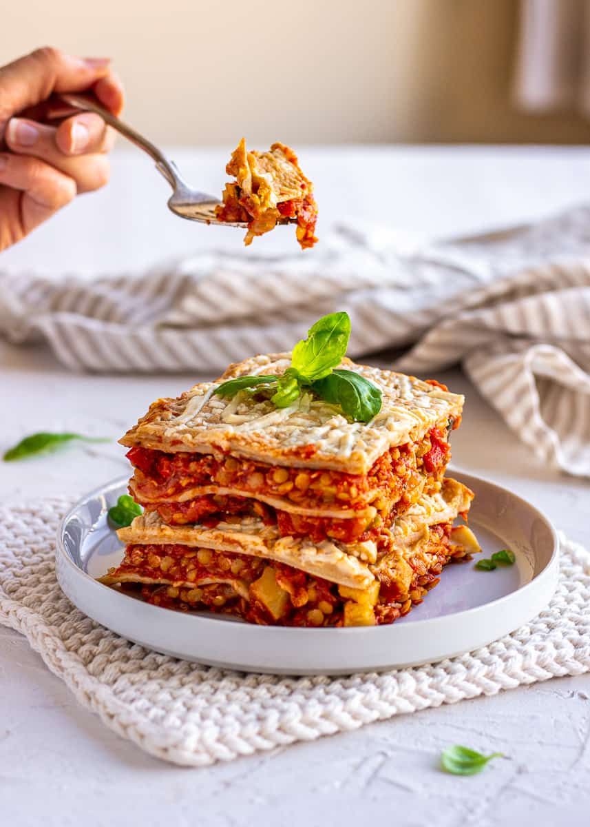 A thick slice of Easy Weeknight Vegan Lasagna is displayed on a white plate. It is topped with basil leaves and the plate is sitting on a white potholder. A woman's hand can be seen holding a forkful of the lasagna.