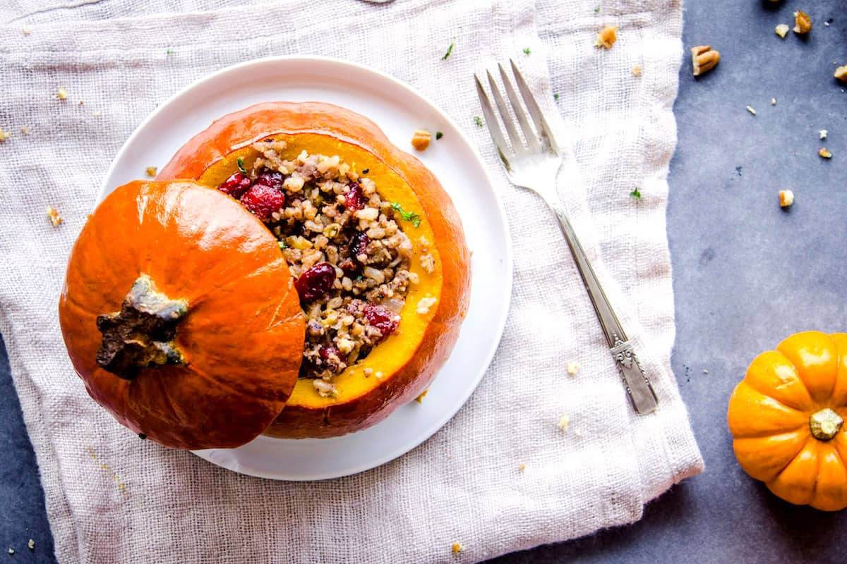 Overhead shot of Stuffed Pumpkin with its lid off, stuffed with cranberries, rice and nuts on a white plate. The plate is on a folded linen napkin which is sitting on a grey table. Around it is a smaller pumpkin, silver cutlery and a dish of pecans.