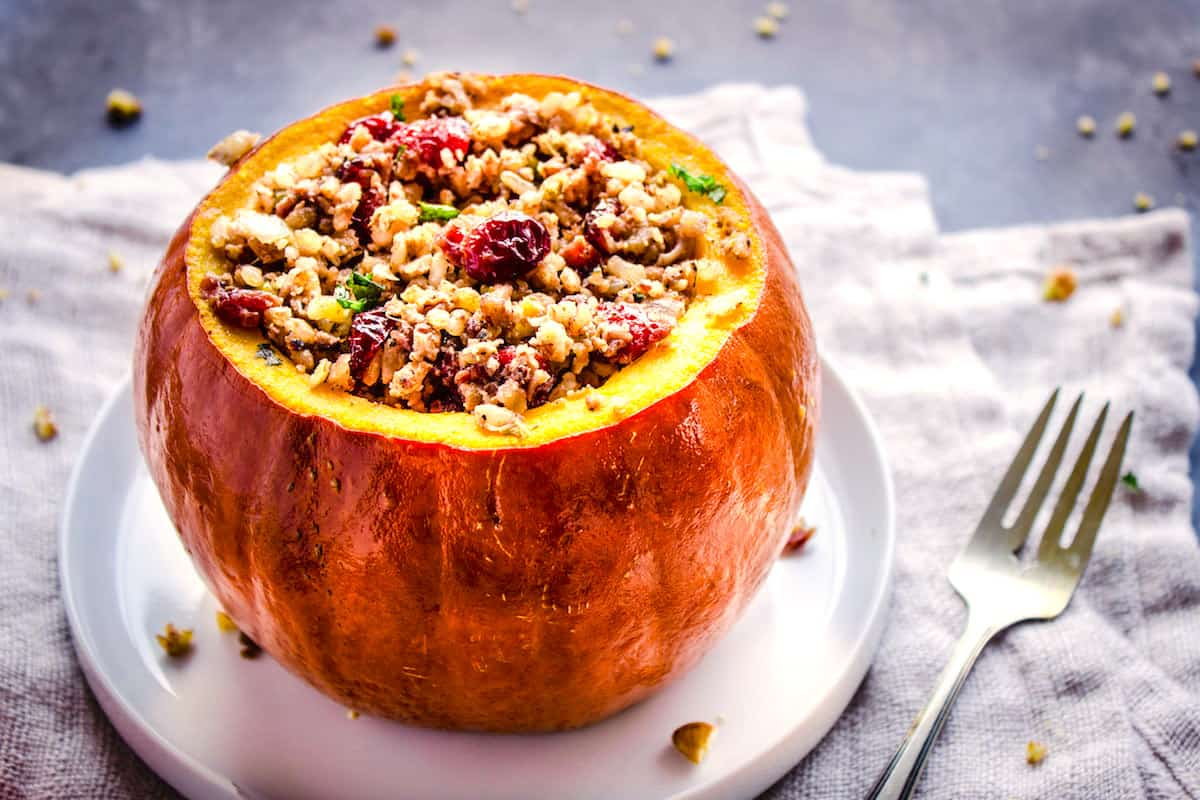 Closeup shot of Stuffed Pumpkin without its lid, stuffed with cranberries, rice and nuts on a white plate. The plate is on a folded linen napkin which is sitting on a grey table. Surrounding it is silver cutlery and pecan crumbs.