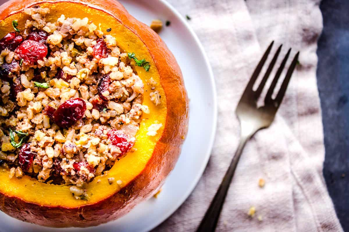 Closeup overhead shot of a pumpkin without its lid, stuffed with cranberries, rice and nuts on a white plate. The plate is on a folded linen napkin which is sitting on a grey table. Surrounding it is a silver fork and pecan crumbs.