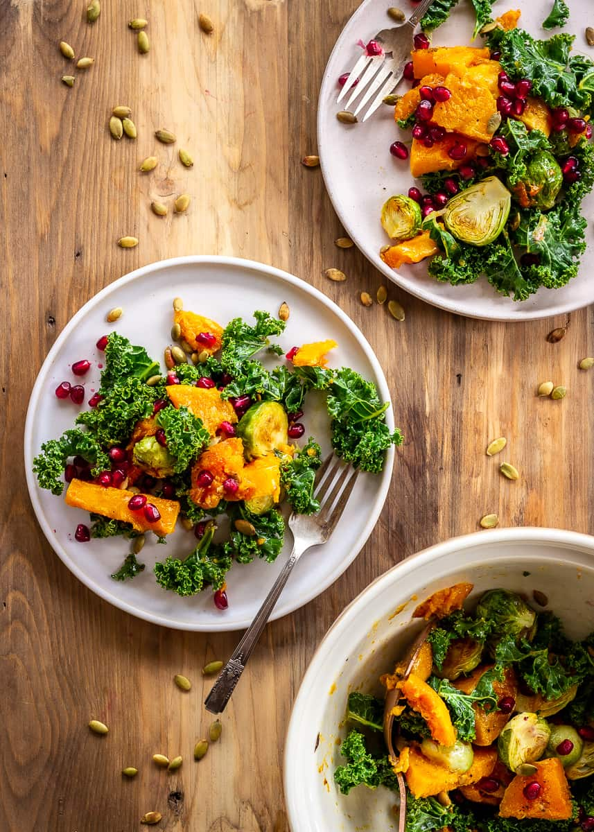 Overhead image of winter salad with roasted butternut squash, Brussels sprouts, kale, pumpkin seeds and pomegranate. Two plates of salad are visible and each have silver forks. They sit on a neutral wooden background with toasted pumpkin seeds scattered around them.