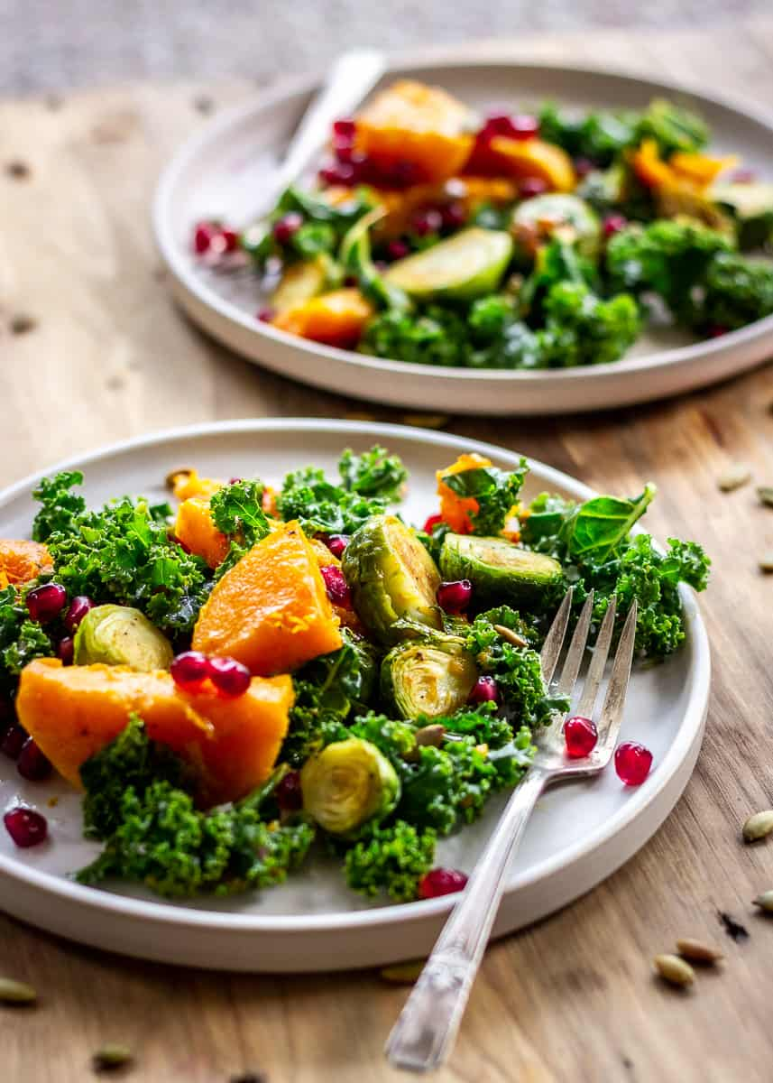 Closeup image of two plates of Brussels sprout salad with roasted butternut squash, kale, pumpkin seeds and pomegranate. Each plate has a silver fork. The plate sits on a neutral wooden background.