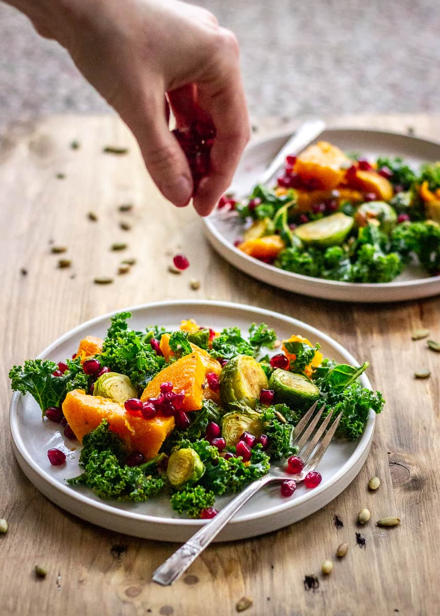 A woman's hand is sprinkling pomegranate seeds over a plate of salad, containing Brussels sprouts, butternut squash and kale. There is a second plate in the background and both plates are on a wooden surface.