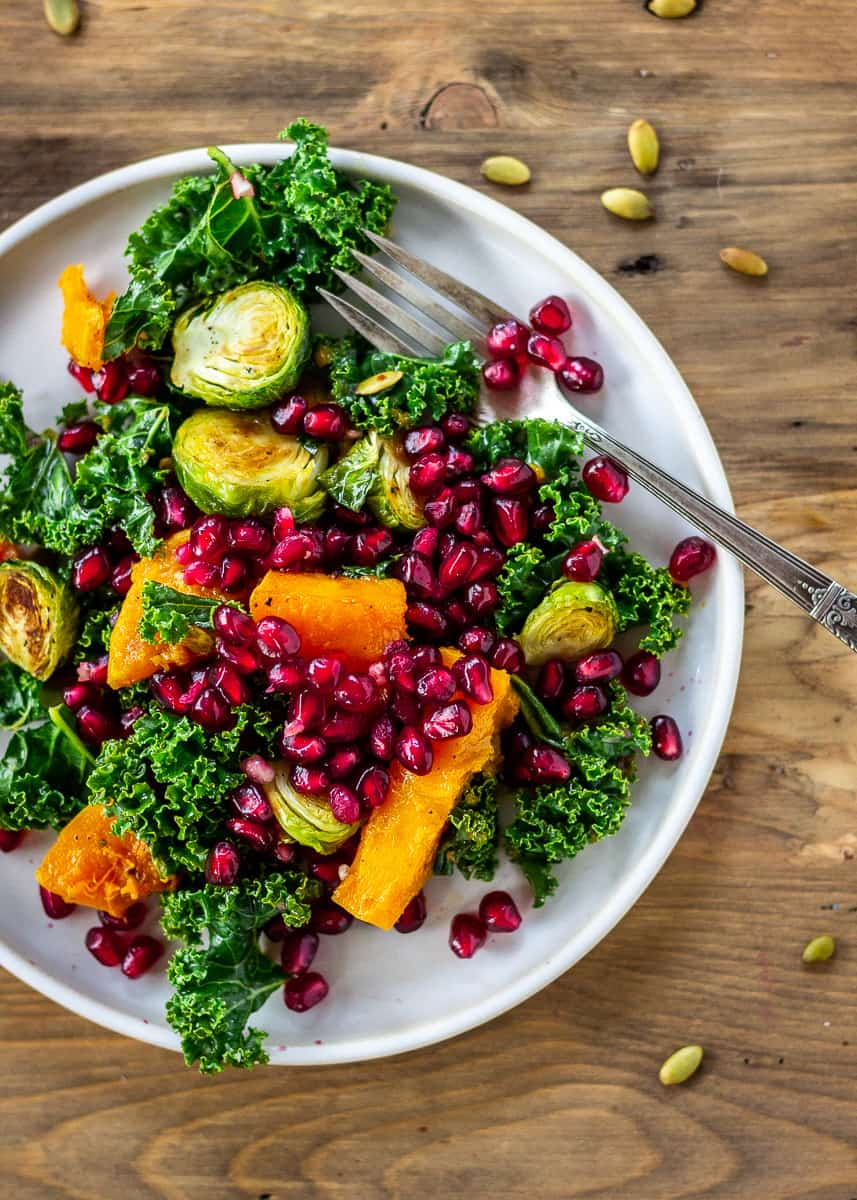 Overhead image of Brussels sprout salad with roasted butternut squash, kale, pumpkin seeds and pomegranate. Salad is on a grey plate with a silver fork. The plate sits on a neutral wooden background.