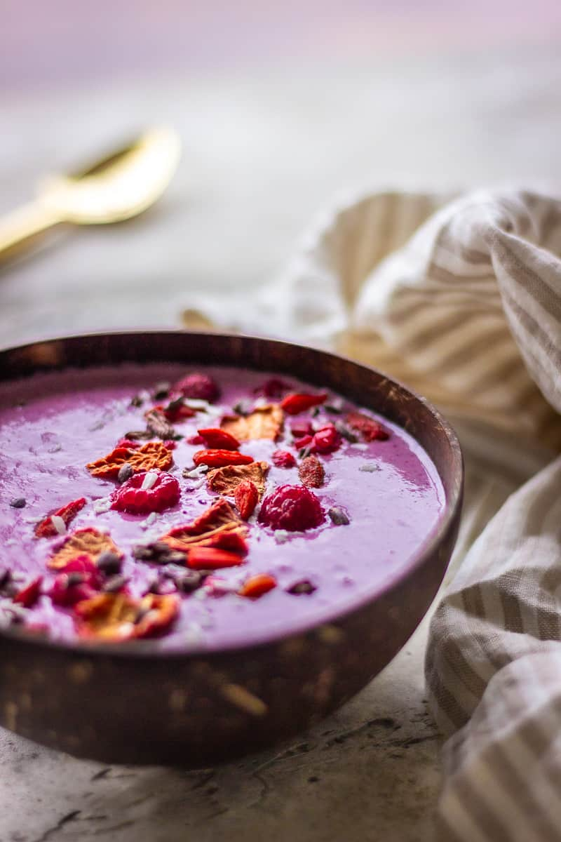 A pink smoothie bowl sits on a neutral grey tabletop. It is decorated with raspberries, freeze-dried strawberries, coconut and cacao nibs. Next to the bowl is a golden spoon and a neutral-coloured striped napkin.
