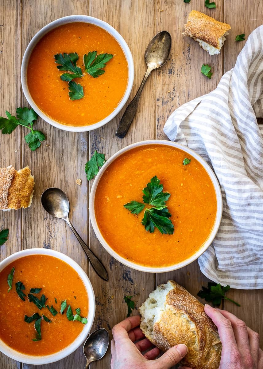 Overhead shot of three bowls of Carrot, Ginger & Apple Soup sit on a wooden background. They are surrounded by bread, parsley leaves, tarnished silver spoons and a striped linen napkin and are decorated with parsley leaves. A woman's hand holds a piece of bread in the bottom right corner.