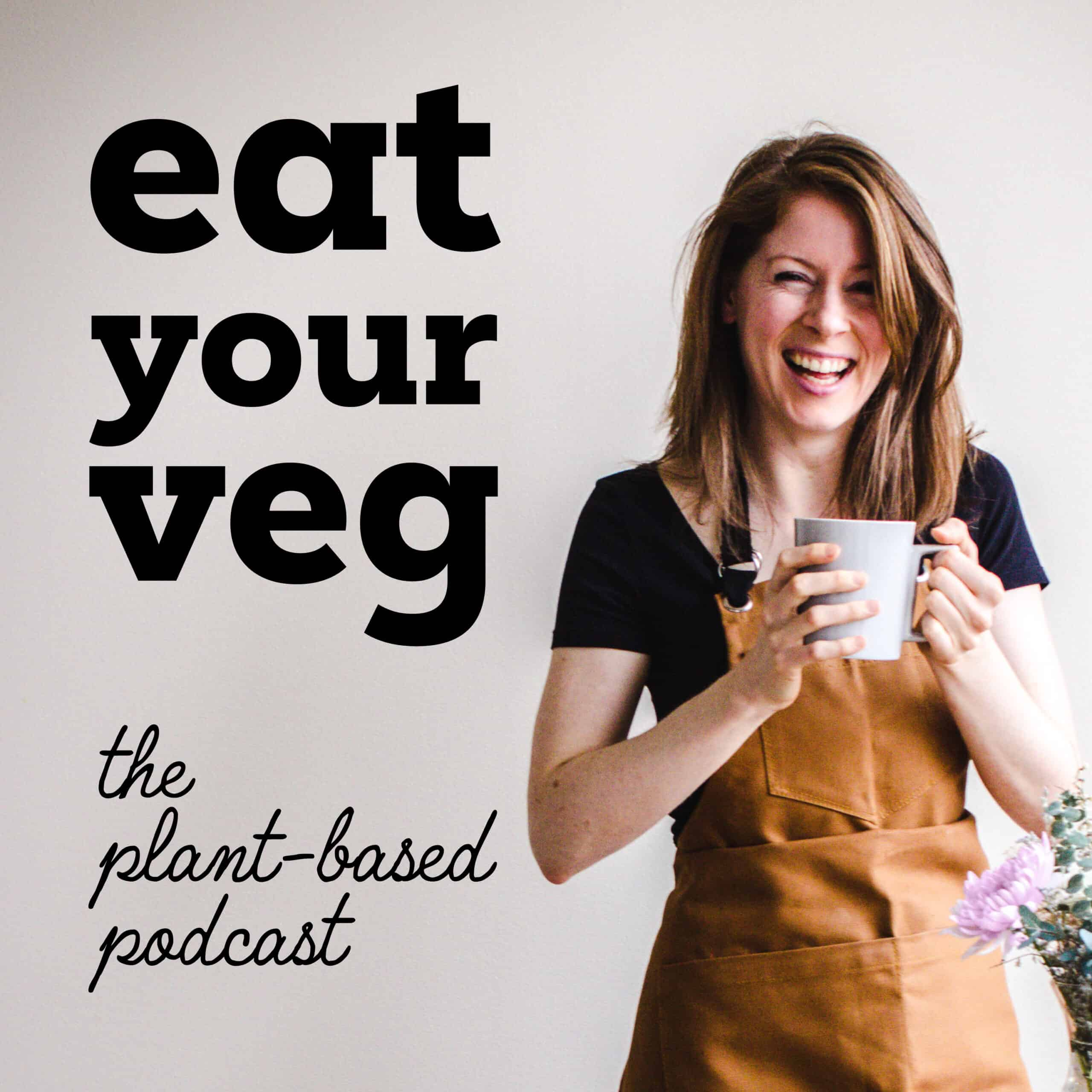 Image shows Elizabeth Emery laughing at the camera, wearing a brown canvas apron. She's holding a large mug of tea and next to her are the words 'Eat Your Veg - The Plant-Based Podcast'.