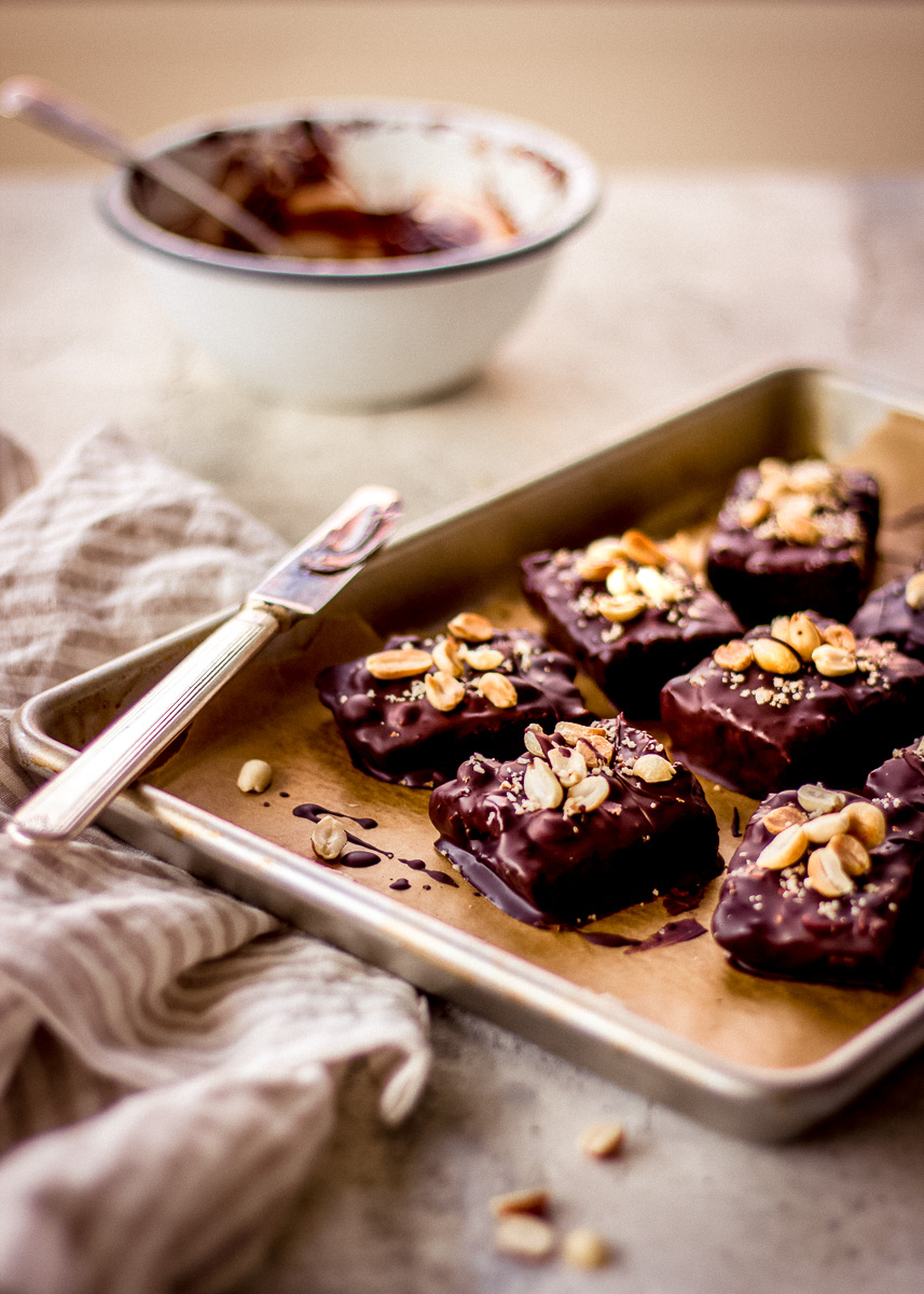 Image of No Bake Vegan Snickers Bars sitting on a kitchen counter, by Vancouver with Love