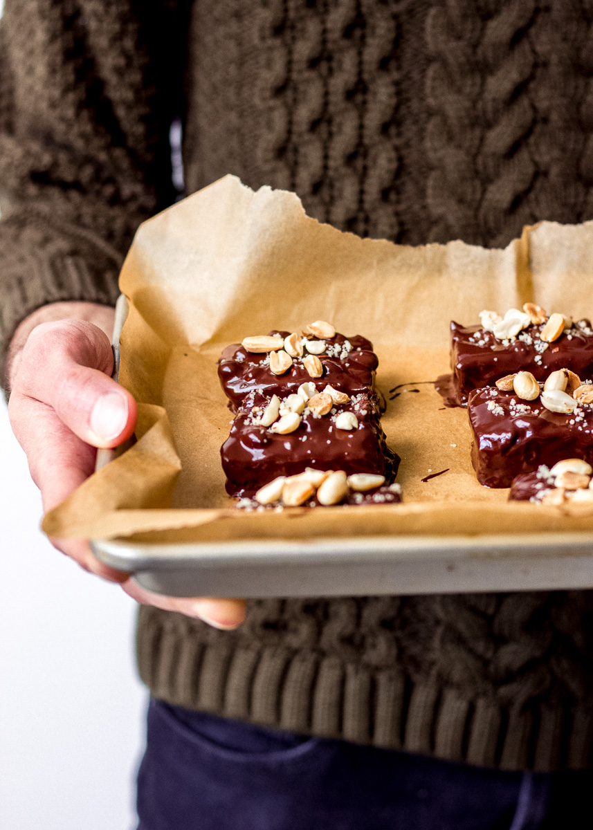 Side on image shows tray of No Bake Vegan Snickers Bars by Vancouver with Love being held by a man in an olive sweater.