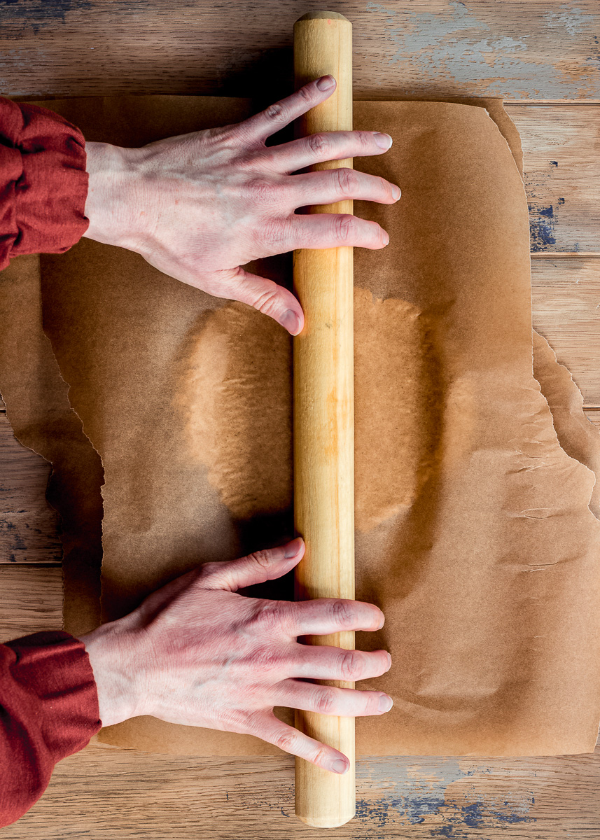 Woman's hands rolling out pastry with a rolling pin on a wooden table.