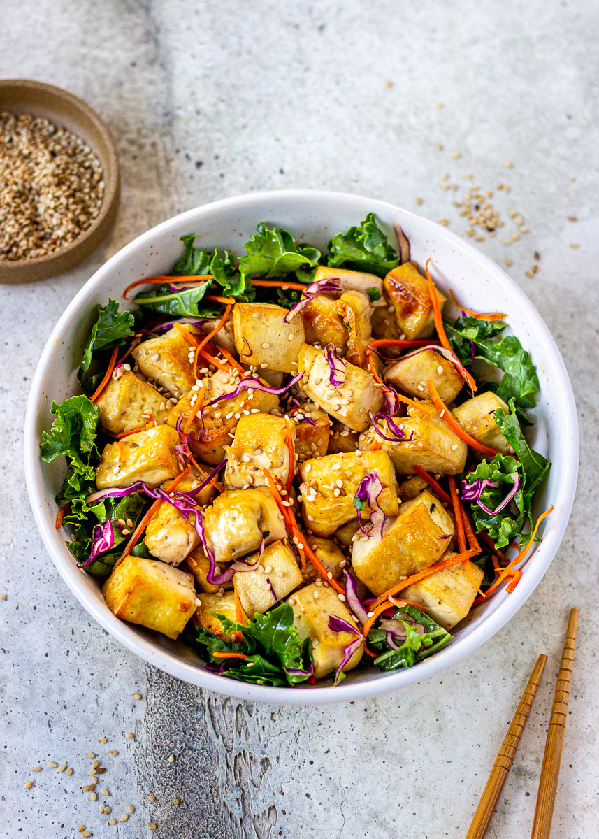 A bowl of Crispy Tofu mixed with kale, carrot, red cabbage and sesame seeds by Vancouver with Love