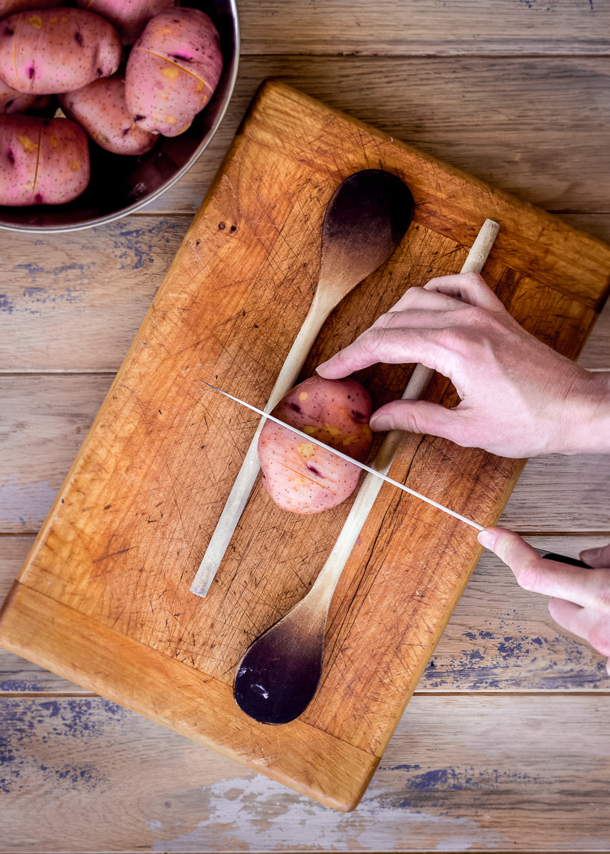 Overhead image showing how to slice potatoes to make hasselback potatoes