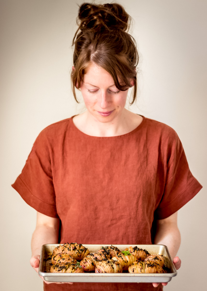Image shows Elizabeth Emery from Vanocuver with Love holding a tray of Sage & Garlic Hasselback Potatoes (vegan and gluten free).