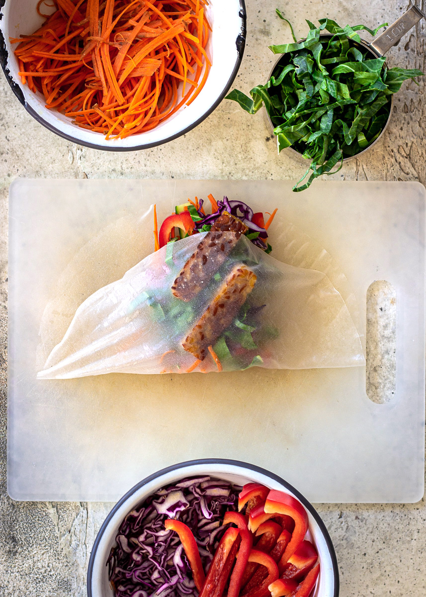 Overhead shot of fresh spring rolls being made with rice wrappers - image shows how to wrap rice wrappers.